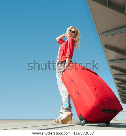 girl goes on vacation with red suitcase - stock photo