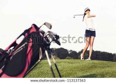 Girl golf player hitting ball on golf course with golf bag in foreground. - stock photo