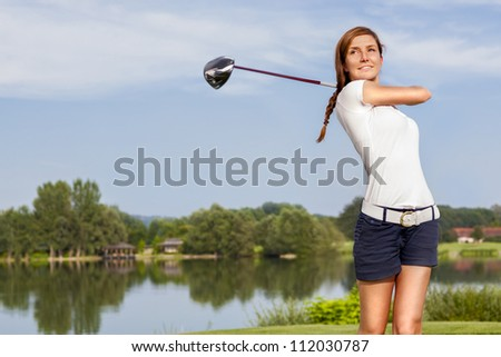 Girl golf player teeing off with driver from tee box, front view. - stock photo