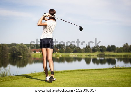 Girl golf player with driver teeing-off from tee-box to shoot over lake, view from behind. - stock photo