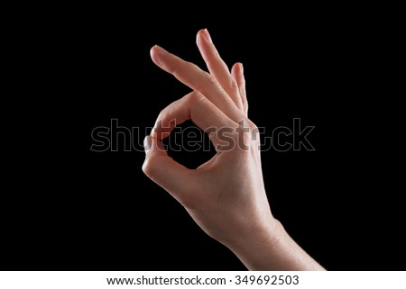 Girl hand gesture is all right everything is OK. Isolated black background. - stock photo