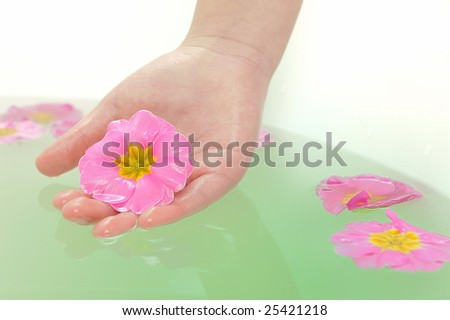 girl Hand holding a pink flower in spa - stock photo