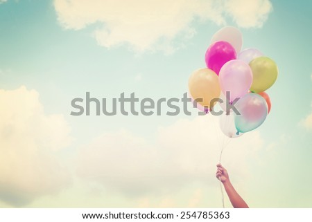 Girl hand holding multicolored balloons done with a retro vintage instagram filter effect, concept of happy birth day in summer and wedding honeymoon party (Vintage color tone) - stock photo