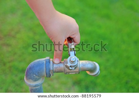 Girl hand open faucet on the grass - stock photo