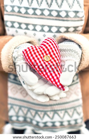 Girl hands in white knitted mittens holding romantic checkered red heart. With love. St. Valentine concept. - stock photo