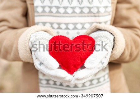 Girl hands in white knitted woolen mittens holding romantic checkered red heart. With love. St. Valentine conceptual horizontal outdoors image. - stock photo