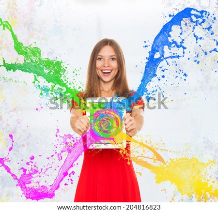 girl happy smile hold tablet screen with splash colorful paint, young woman wear red dress - stock photo