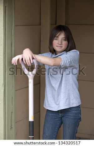 Girl has arms on shovel. - stock photo