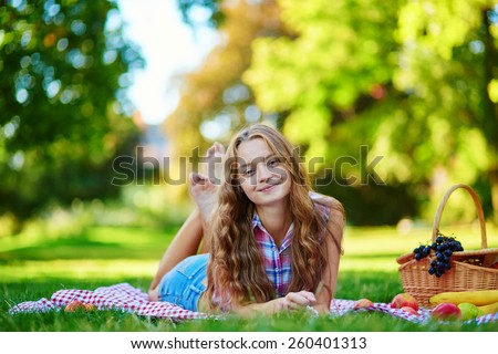 Girl having a picnic in park, lying on the grass, picnic basket with fruits near her - stock photo