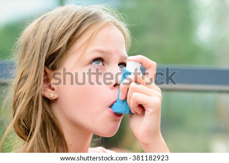 Girl having asthma allergy using the asthma inhaler for being healthy - shallow depth of field - stock photo