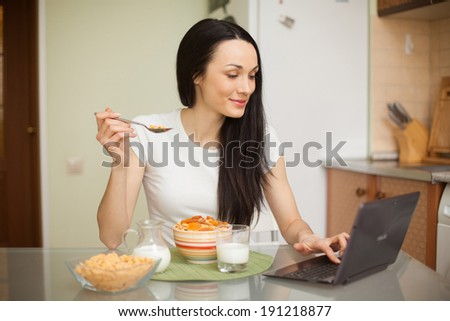 girl having breakfast and using her laptop in the kitchen at home  - stock photo