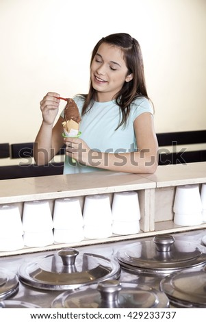 Girl Having Chocolate Ice Cream At Counter - stock photo