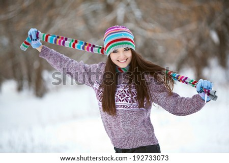 Girl having fun in the snow in a cap and gloves - stock photo