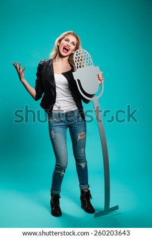 girl having fun in the studio with a fake microphone. musical instruments, concept, rock, blonde - stock photo
