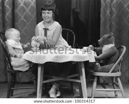 Girl having tea party with doll and bear - stock photo