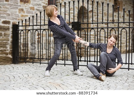 Girl helping her sister to get up - stock photo