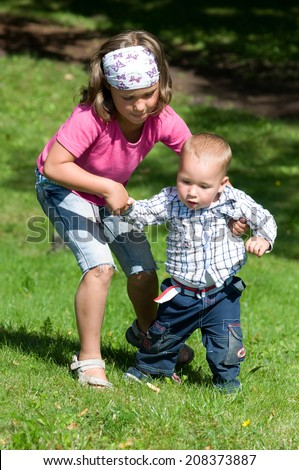 Girl helps her little brother while running - stock photo