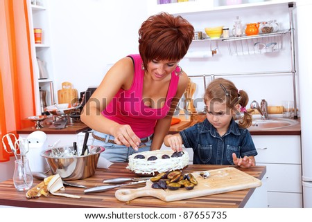 Girl helps her mother decorating the plum cake - stock photo