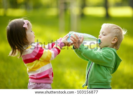 Girl helps the boy to keep a bottle - stock photo