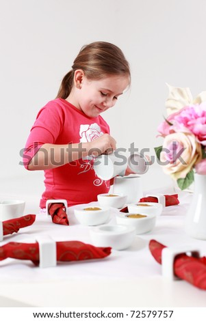Girl helps to set the table - pouring tea - stock photo