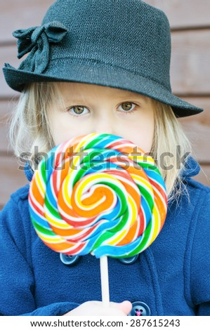 Girl hiding behind a huge lollypop - stock photo