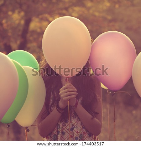 Girl hiding behind the balloon - stock photo