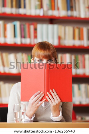 Girl hiding behind the book on library - stock photo
