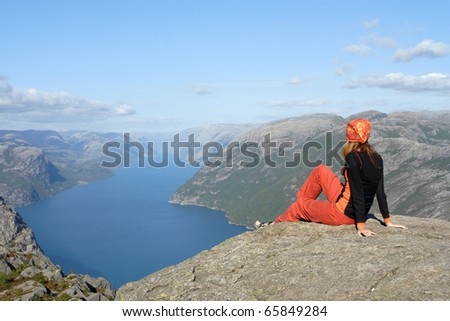 girl hiker sitting on a brink rock and looking at the mountains - stock photo