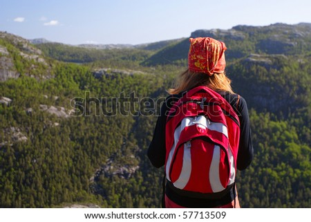 girl hiker standing on a rock and looking at the mountains - stock photo