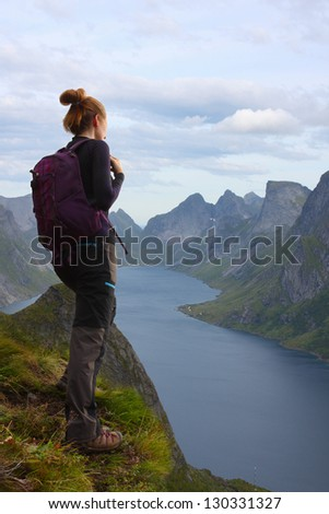 girl hiker standing on cliff and looking at the mountains,  lofoten, norway - stock photo
