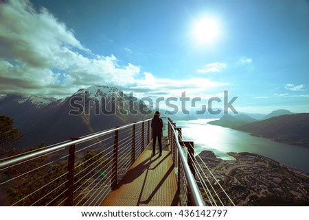 girl hiker with a backpack standing on  viewing platform and looking on Romsdalsfjorden and Andalsnes, Norway - stock photo