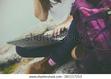 girl hiker with a laptop sitting on a rock on a background of mountains and lakes - stock photo