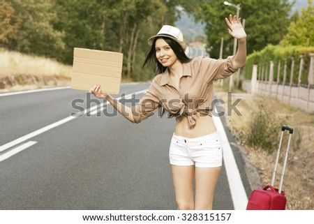 girl hitchhiking on the road - stock photo