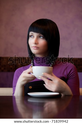 girl hold cup of coffee in hand thoughtful - stock photo