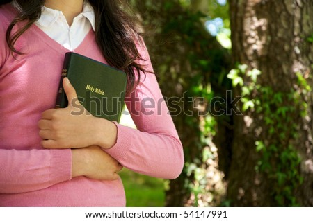 Girl holding a Bible in nature - stock photo