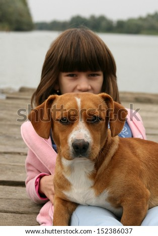 Girl holding a dog in her lap next to river - stock photo