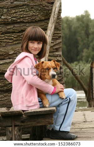 Girl holding a dog in her lap next to wooden house - stock photo