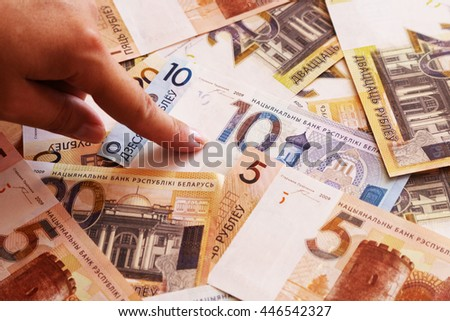 girl holding a finger over the new money of the Republic of Belarus - stock photo