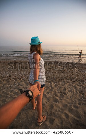 Girl holding a hand man on the beach - stock photo