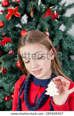 Girl holding a ornament of the christmas tree - stock photo