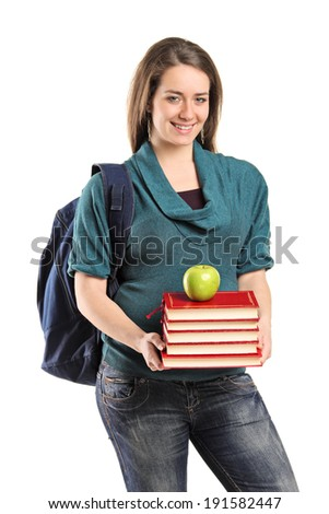 Girl holding a stack of books and an apple on top isolated on white background - stock photo