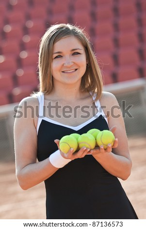 Girl holding a tennis balls while standing on a tennis court for lessons. - stock photo