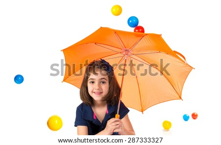Girl holding an umbrella while raining colored balls - stock photo
