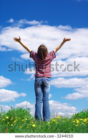 girl holding arms up in praise against blue sky - stock photo