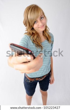 Girl Holding Cellphone. Thirteen year old girl holding her cellphone toward the viewer. Focus on model. Note: Not Isolated. - stock photo