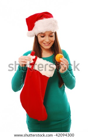 Girl holding christmas sock and clementine on white background - stock photo