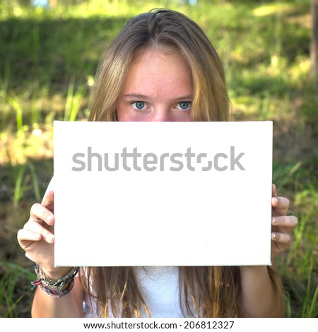 Girl holding clean white sheet paper, in the park (banner for message) - stock photo
