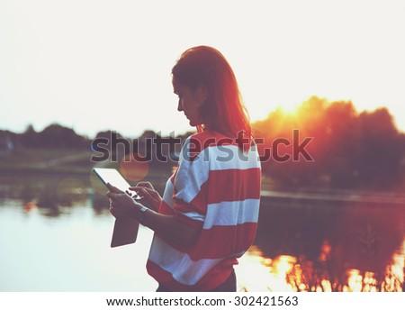 girl holding digital tablet pc at lake shore in sunrise light - stock photo