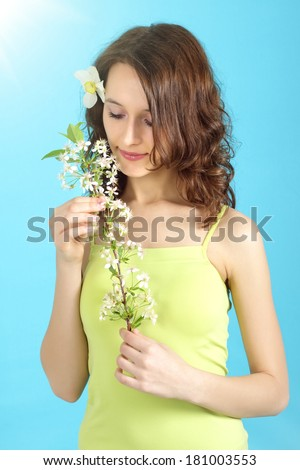 girl holding flower cherry on a blue background - stock photo