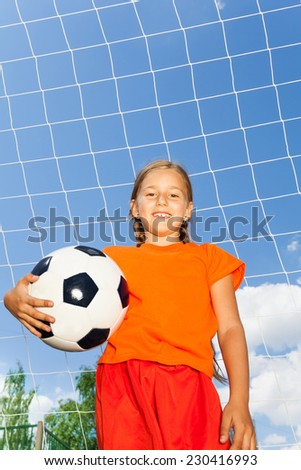 Girl holding football in one arm standing in front of white net of woodwork on sky background - stock photo